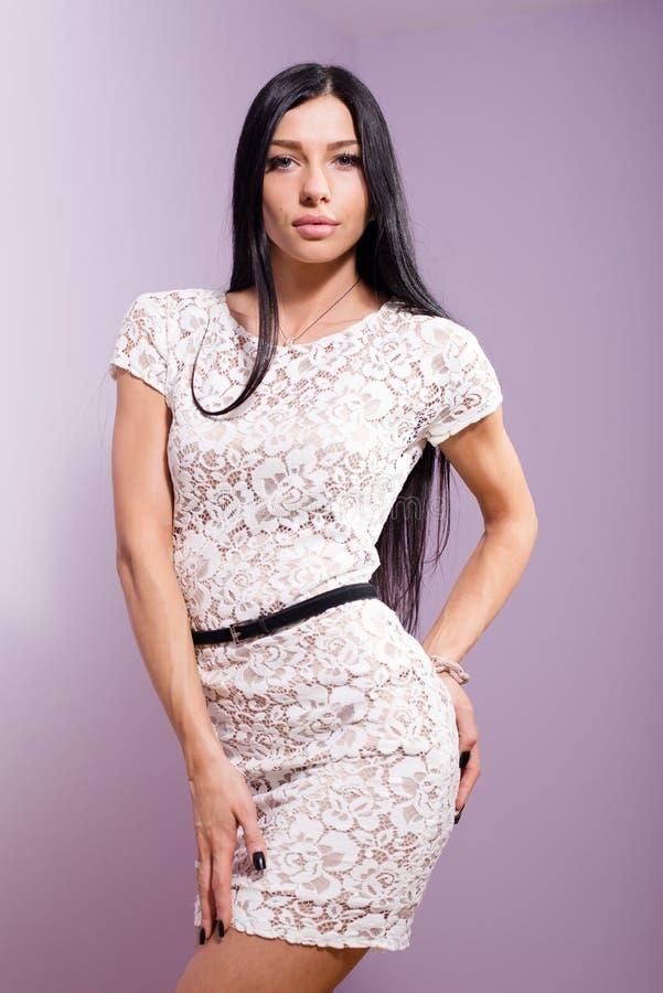 Portret van mooie donkerbruine jonge vrouw in het witte kantkleding stellen stock afbeelding