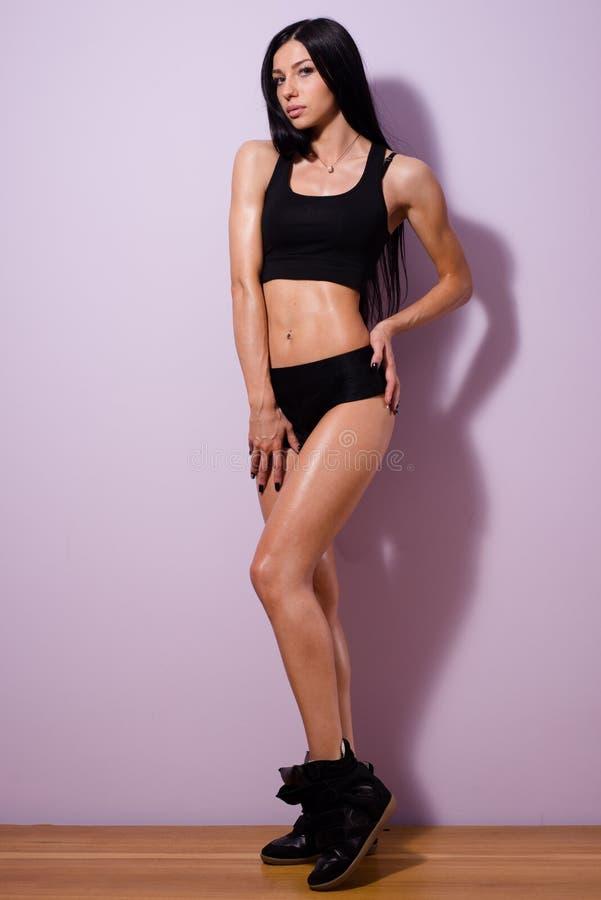 Portret van mooie donkerbruine jonge vrouw met het perfecte cijfer glimlachen die zich in zwarte sportwear en giechels op violett royalty-vrije stock foto's