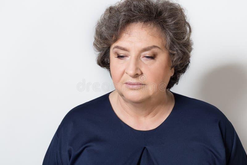 Portret van mooie elegante vrouw in een well-kept oudere srudii op een witte achtergrond met make-up en zonder make-up stock foto