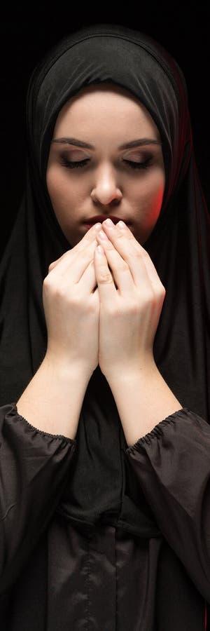 Portret van mooie ernstige jonge moslimvrouw die zwarte hijab met handen dragen dichtbij haar gezicht als het bidden van concept stock afbeelding
