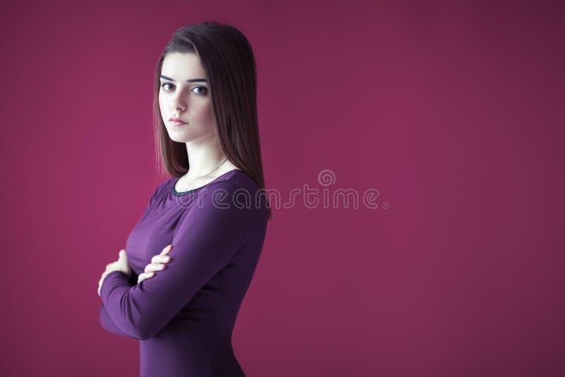 Portret van mooie ernstige vrouw met gekruiste wapens op roze bedelaars royalty-vrije stock foto's