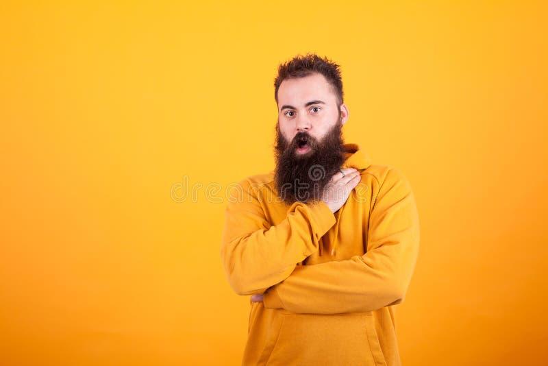 Portret van mooie gebaarde hipster kijken die die over gele achtergrond wordt verbaasd stock foto