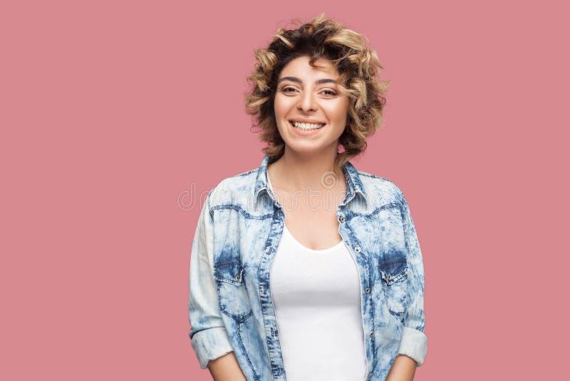 Portret van mooie gelukkige jonge vrouw met make-up en krullend kapsel in toevallig blauw overhemd die en zich camera bevinden be stock foto's