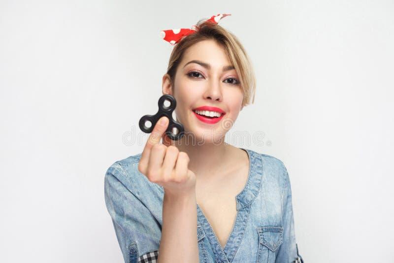 Portret van mooie gelukkige jonge vrouw in toevallig blauw denimoverhemd met make-up en rode hoofdband die en handspinner bevinde royalty-vrije stock fotografie