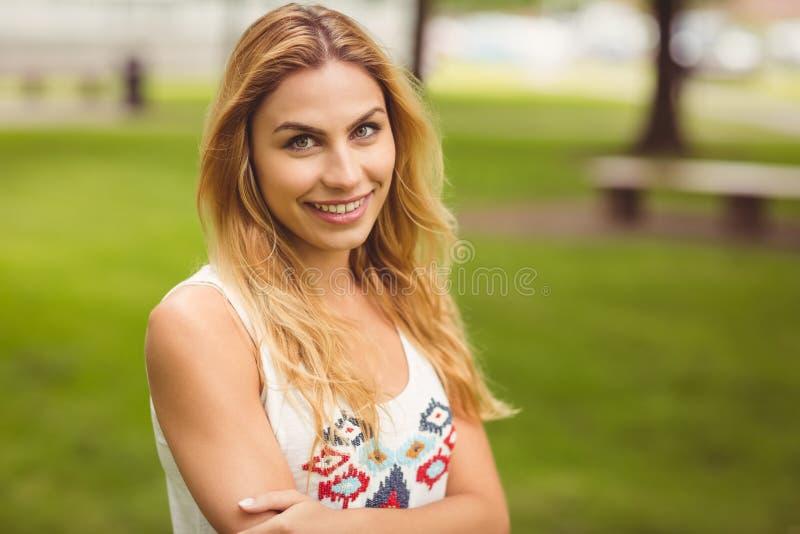 Portret van mooie glimlachende die vrouw met wapens in park worden gekruist royalty-vrije stock foto