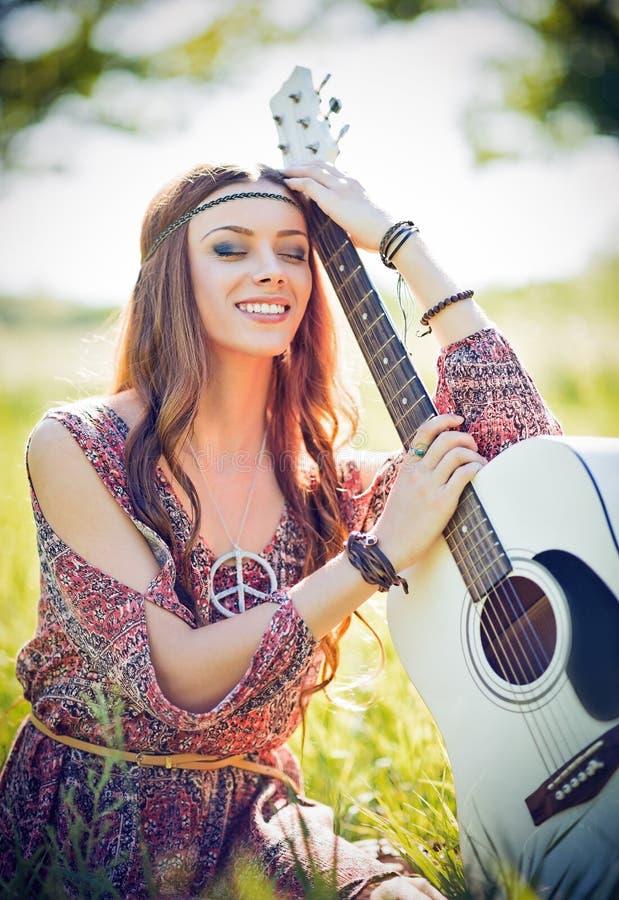 Portret van mooie glimlachende hippievrouw met gitaar Mistig dalingseiland royalty-vrije stock fotografie