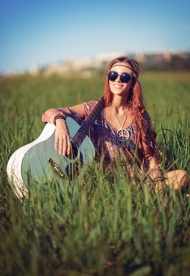 Portret van mooie glimlachende hippievrouw met gitaar op het gebied royalty-vrije stock fotografie