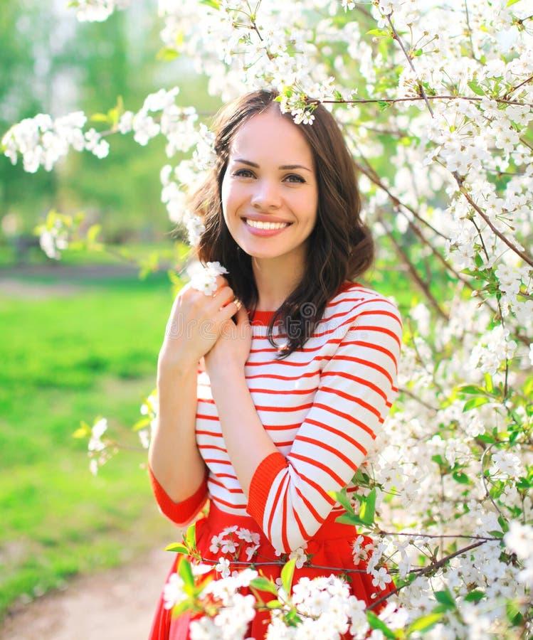Portret van mooie glimlachende jonge vrouw in bloeiende de lentetuin royalty-vrije stock foto