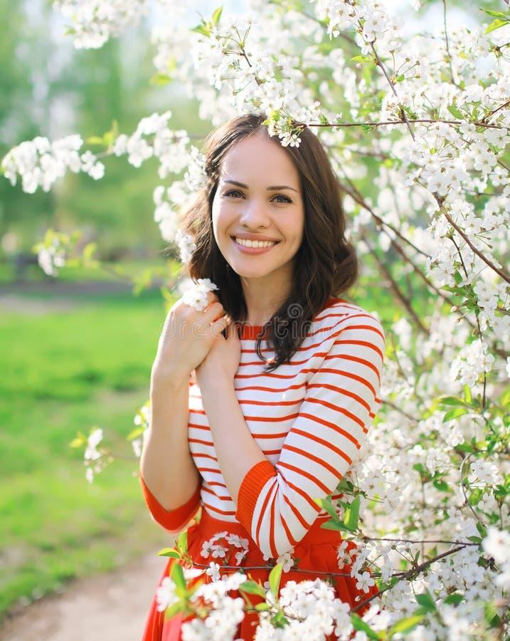 Portret van mooie glimlachende jonge vrouw in bloeiende tuin stock fotografie