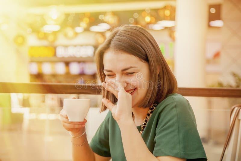 Portret van mooie glimlachende jonge vrouw met koffiekop in cof stock afbeelding