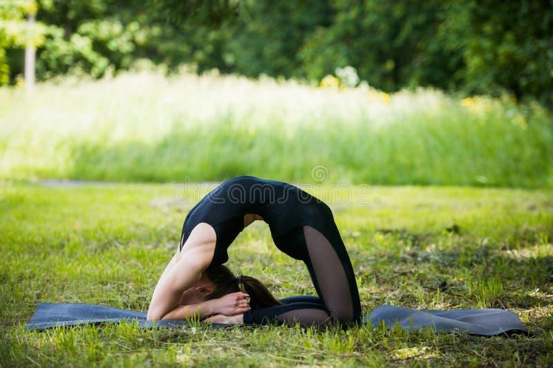 Portret van mooie glimlachende sportieve geschikte blonde jonge vrouw die bikram yoga backbend op de zomerdag doen, volledige Nat stock afbeelding