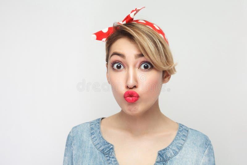 Portret van mooie grappige jonge vrouw in toevallig blauw overhemd met make-up, rode hoofdband status, die camera met grote ogen  royalty-vrije stock fotografie