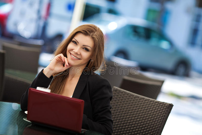 Portret van mooie het glimlachen vrouwenzitting in een koffie met openlucht laptop royalty-vrije stock foto's