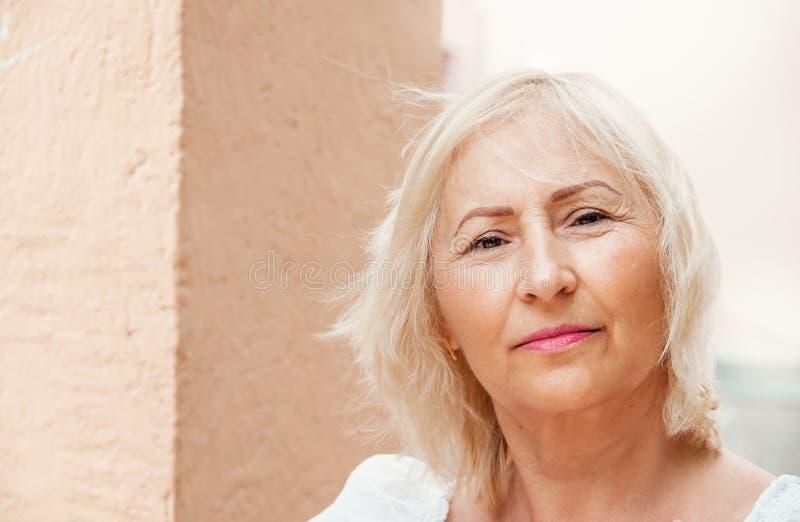 Portret van mooie hogere vrouw met wit haar die zich door w bevinden stock foto's