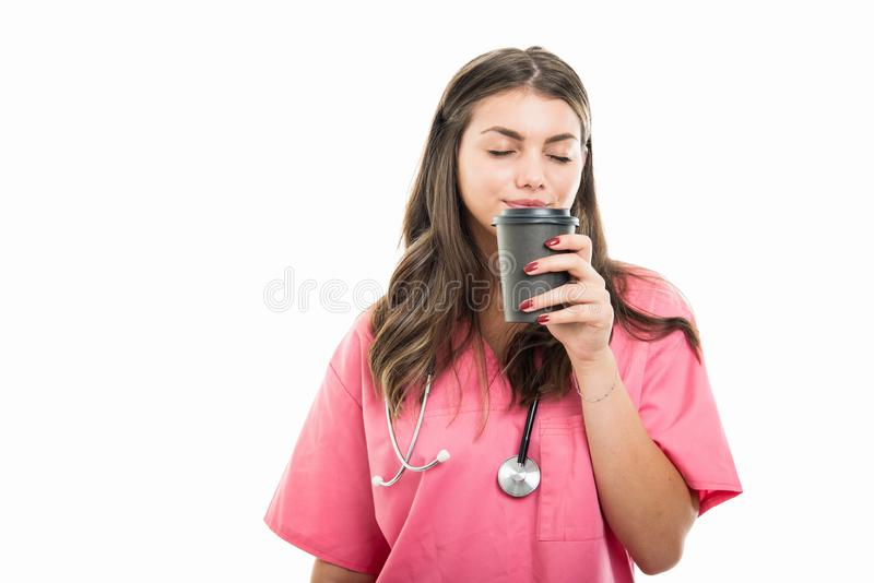 Portret van mooie jonge arts die meeneemkoffie ruiken stock afbeelding