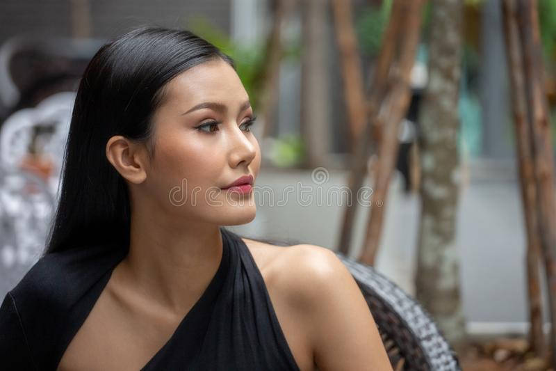 Portret van mooie jonge Aziatische vrouw in een zwarte kleding die weg openlucht in stad kijken royalty-vrije stock afbeelding