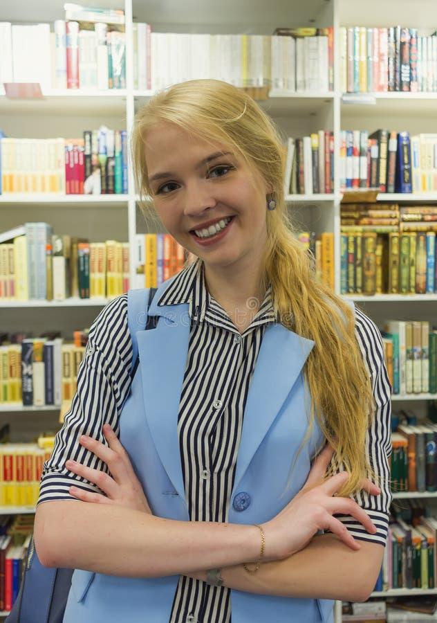 Portret van mooie jonge blonde Europese student in een bibliotheek royalty-vrije stock foto
