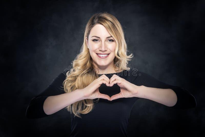 Portret van mooie jonge blonde vrouw die hartteken tonen royalty-vrije stock foto's