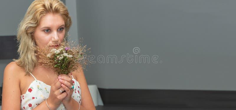 Portret van mooie jonge blondevrouw met boeket van bloemen royalty-vrije stock afbeeldingen