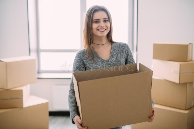 Portret van mooie jonge donkerbruine verpakking die sommige dozen zich in haar nieuw huis dragen te bewegen stock afbeelding