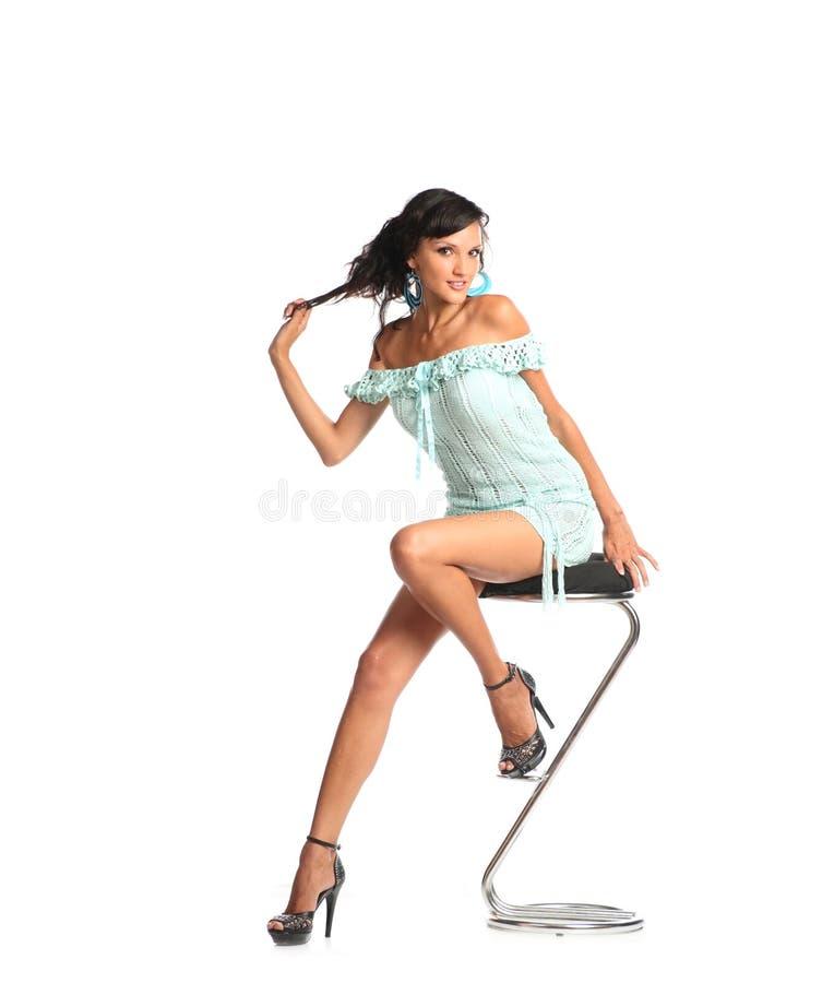 Portret van mooie jonge donkerbruine vrouw die in modieuze kleding en zwarte schoenen op barstoel zitten royalty-vrije stock foto
