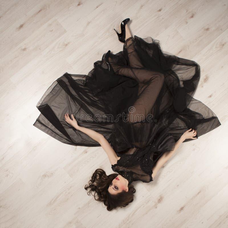 Portret van mooie jonge donkerbruine vrouwenprinses in zwarte kleding die op vloer liggen stock fotografie