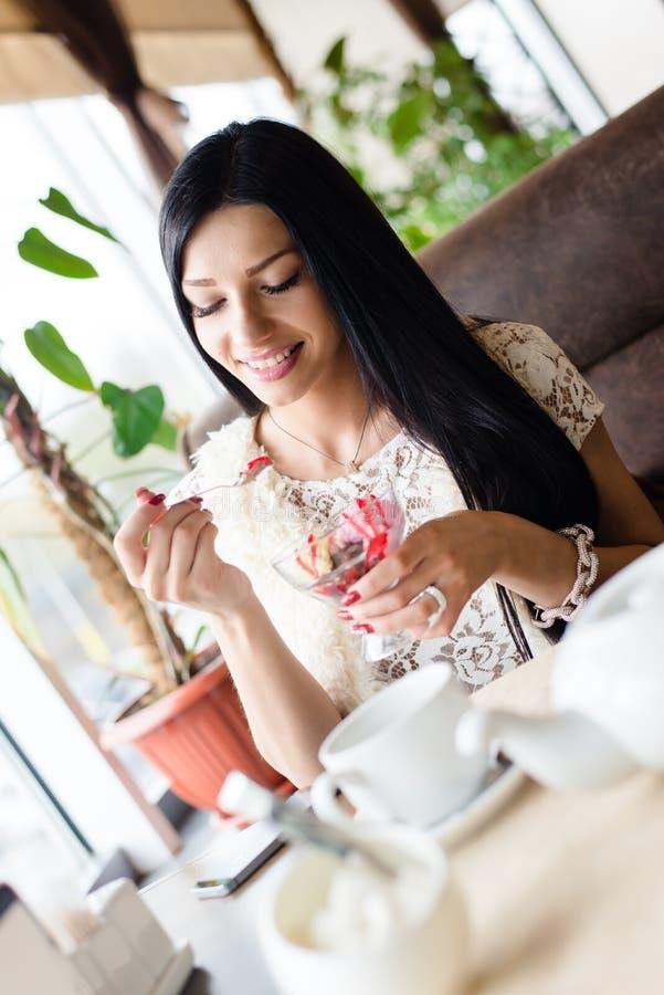 Portret van mooie jonge gelukkige glimlachende vrouw die pret hebben die roomijs in koffiewinkel of restaurant eten stock fotografie