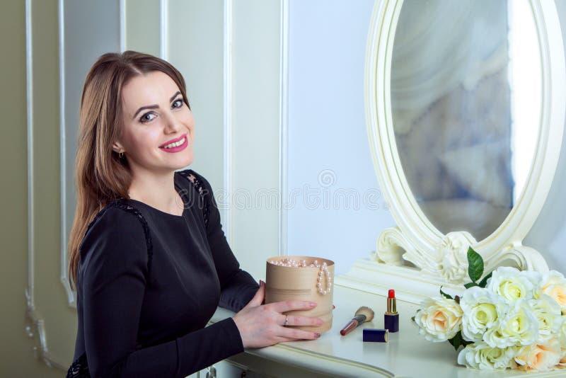 Portret van mooie jonge het glimlachen donkerbruine vrouwenzitting dichtbij spiegel stock afbeelding