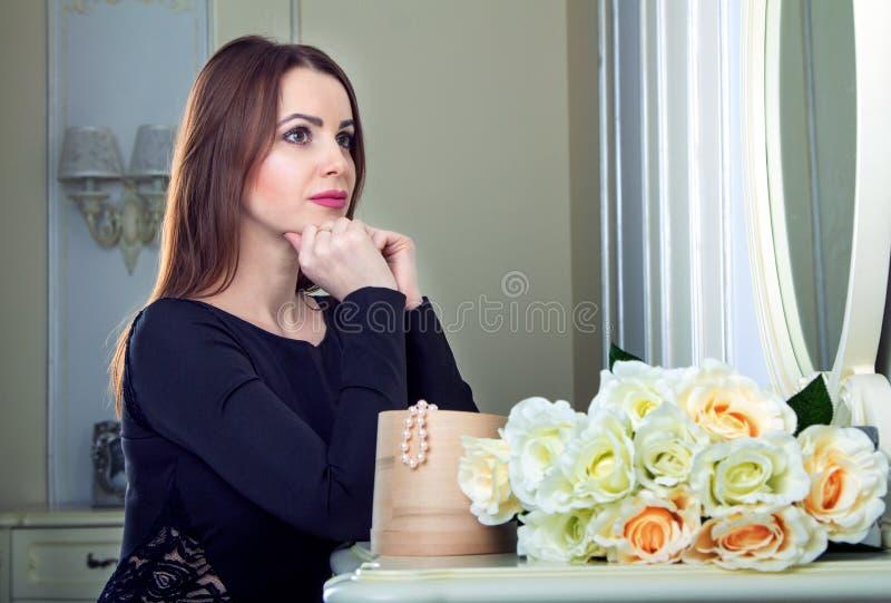 Portret van mooie jonge het glimlachen donkerbruine vrouwenzitting dichtbij spiegel royalty-vrije stock foto's