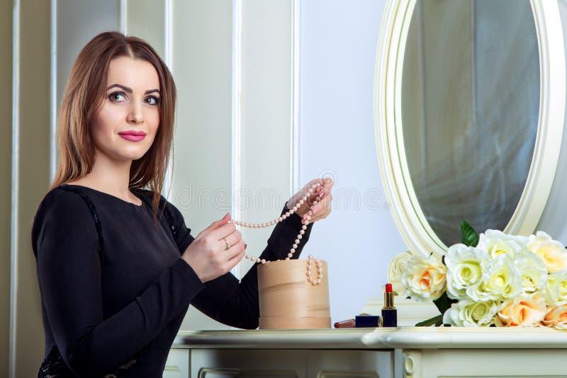 Portret van mooie jonge het glimlachen donkerbruine vrouwenzitting dichtbij spiegel stock fotografie