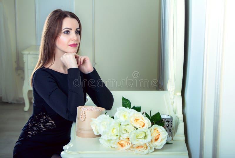 Portret van mooie jonge het glimlachen donkerbruine vrouwenzitting dichtbij spiegel royalty-vrije stock fotografie