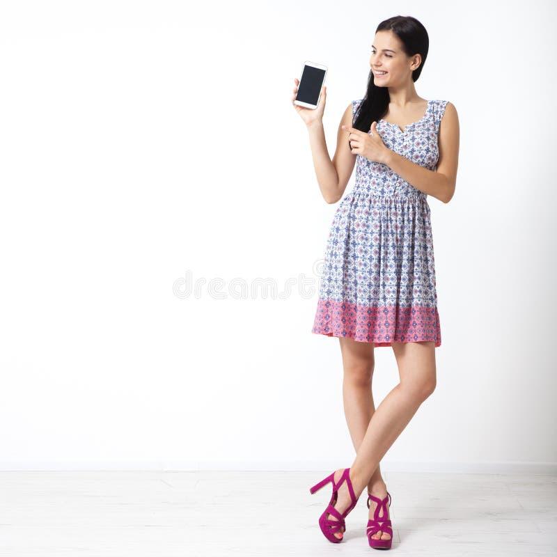 Portret van mooie jonge smartphone van de vrouwenholding op witte achtergrond stock foto's