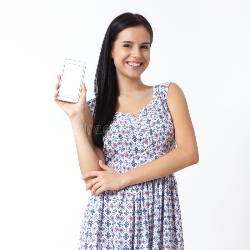 Portret van mooie jonge smartphone van de vrouwenholding op witte achtergrond royalty-vrije stock foto