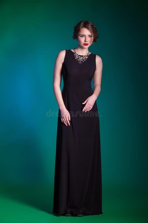 Portret van mooie jonge vrouw in avond zwarte kleding stock foto's