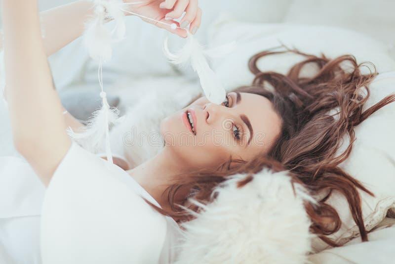 Portret van mooie jonge vrouw in bohostijl met veer Het liggen op bed De gelukkige jonge zakken van de meisjesholding op een witt royalty-vrije stock foto