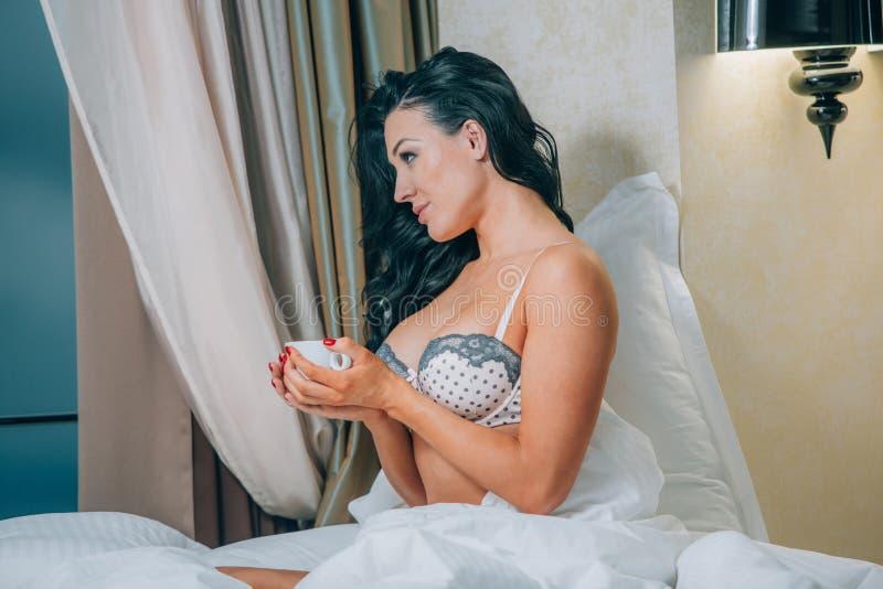 Portret van mooie jonge vrouw in de koffiekop van de nachthemdenholding op bed stock foto