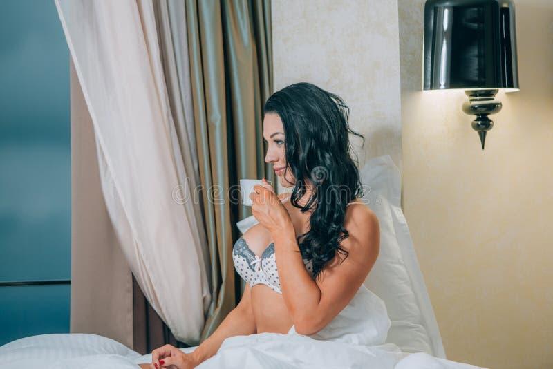 Portret van mooie jonge vrouw in de koffiekop van de nachthemdenholding op bed stock afbeelding
