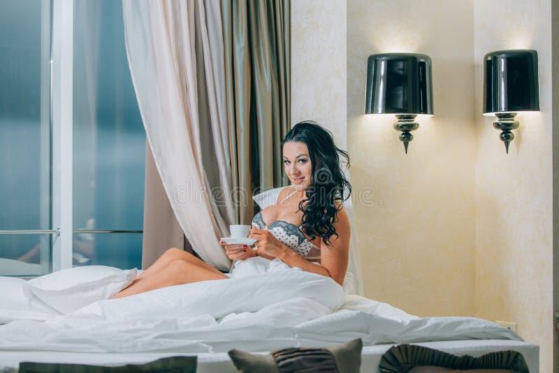 Portret van mooie jonge vrouw in de koffiekop van de nachthemdenholding op bed stock foto's