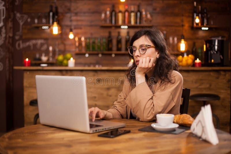Portret van mooie jonge vrouw die aan haar laptop in een koffiewinkel werken stock fotografie
