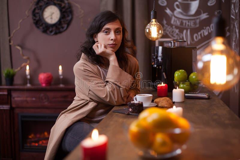 Portret van mooie jonge vrouw die camera bekijken en bij de barteller zitten in een winkel van de elengatkoffie royalty-vrije stock afbeeldingen