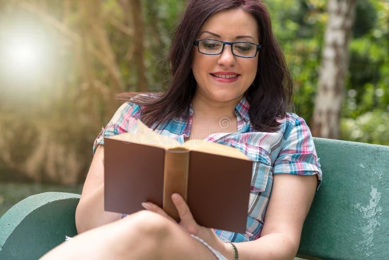 Portret van mooie jonge vrouw die een boek op een bank in park, lichteffect lezen stock afbeelding