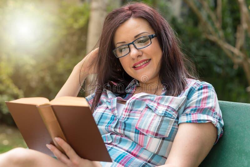 Portret van mooie jonge vrouw die een boek op een bank in park, lichteffect lezen stock fotografie