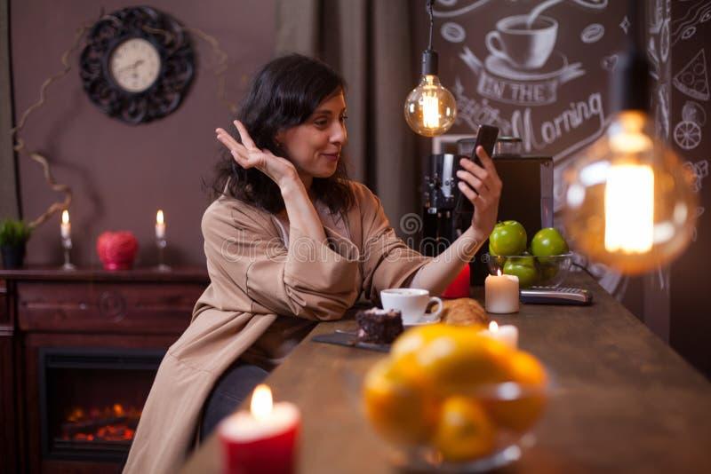 Portret van mooie jonge vrouw die een videogesprek hebben terwijl het zitten bij de barteller in een koffiewinkel royalty-vrije stock fotografie