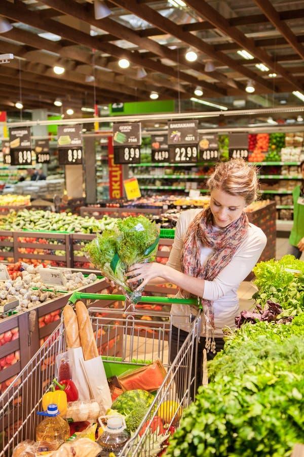 Portret van mooie jonge vrouw die groene bladgroente kiezen stock foto