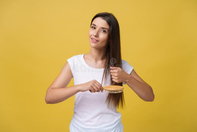 Portret van mooie jonge vrouw die haar haar, het bekijken camera en het glimlachen kammen royalty-vrije stock fotografie