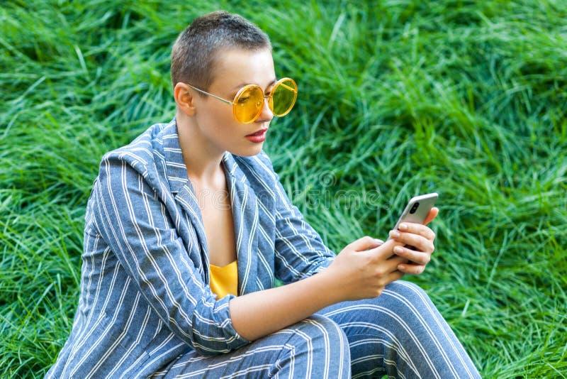 Portret van mooie jonge vrouw die met kort haar in toevallig blauw gestreept kostuum, gele glazen op groen gras zitten die haar h stock foto's