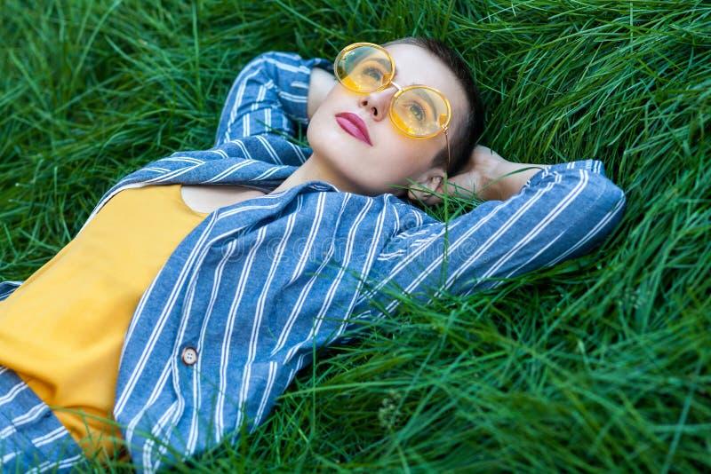 Portret van mooie jonge vrouw die met kort haar in toevallig gestreept kostuum, geel overhemd, glazen op groen gras, het rusten l royalty-vrije stock foto
