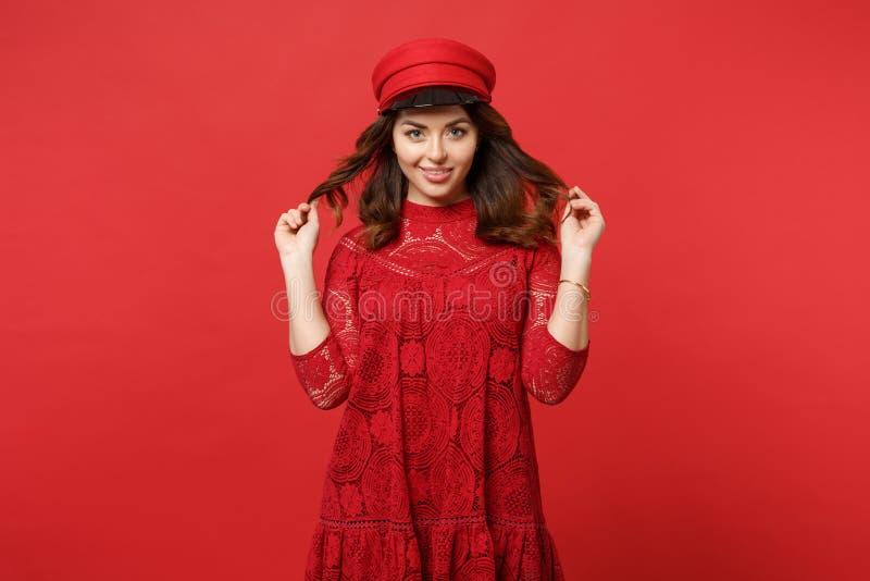 Portret van mooie jonge vrouw in kantkleding en GLB-holdingshaar die camera kijken die op heldere rode muur wordt geïsoleerd stock foto's