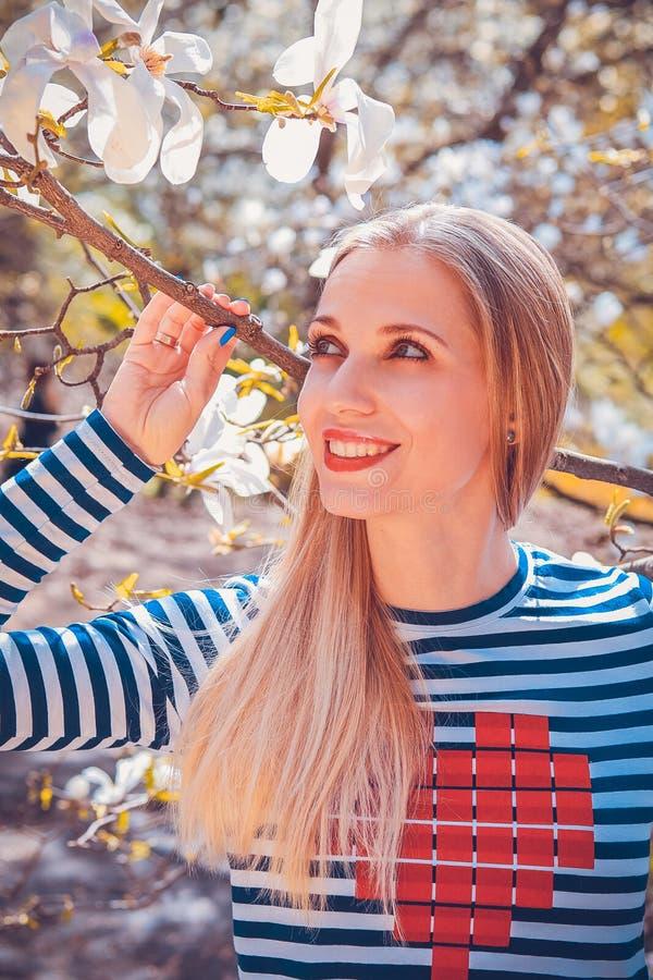 Portret van mooie jonge vrouw in Magnolia bloeiend park op een zonnige dag Glimlachend meisje met Magnoliabloemen Gelukkig meisje royalty-vrije stock afbeeldingen