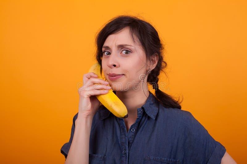 Portret van mooie jonge vrouw met ernstig gezicht die een banaan houden en de camera in studio over geel bekijken stock foto's